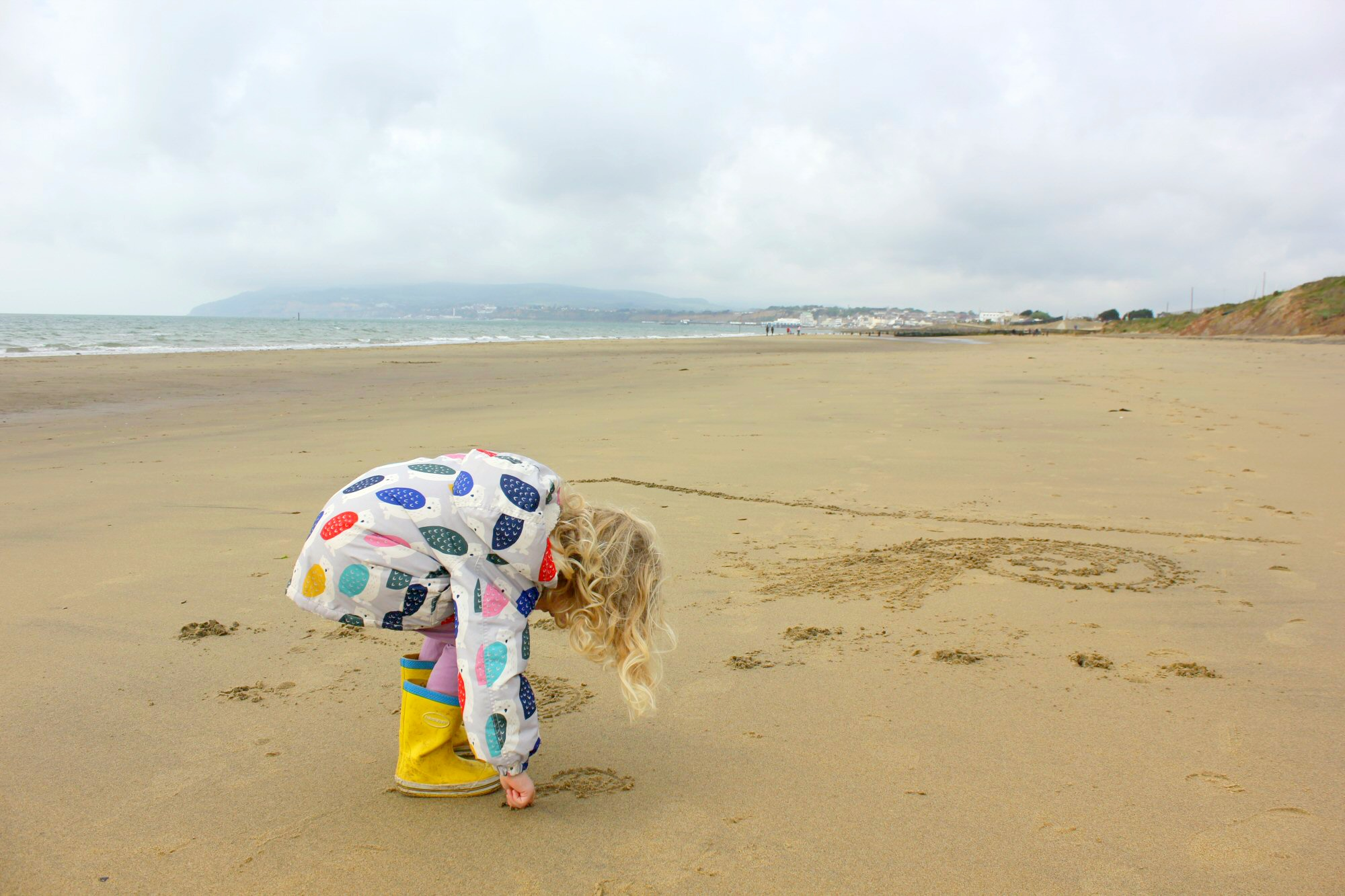 My daughter drawng shapes in the sand on our fossil walk at Yaverland beach - hunting the Isle of Wight dinosaurs