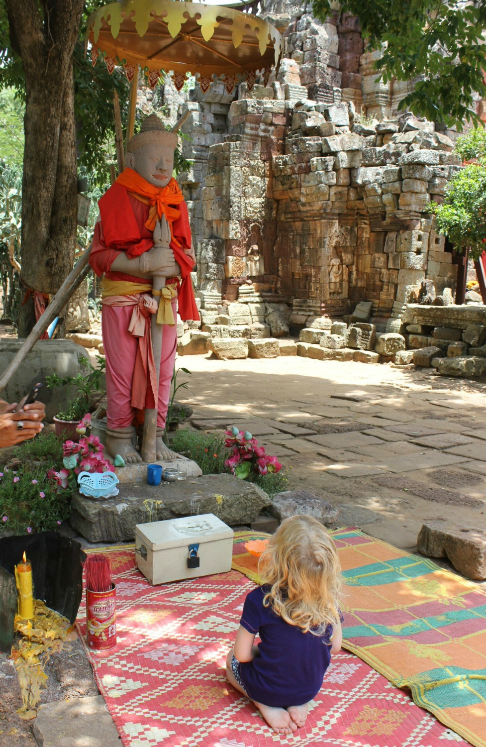 My daughter kneels in front of a Buddha statue at Banan temple, near Battambang - 12 reasons to visit Cambodia with kids