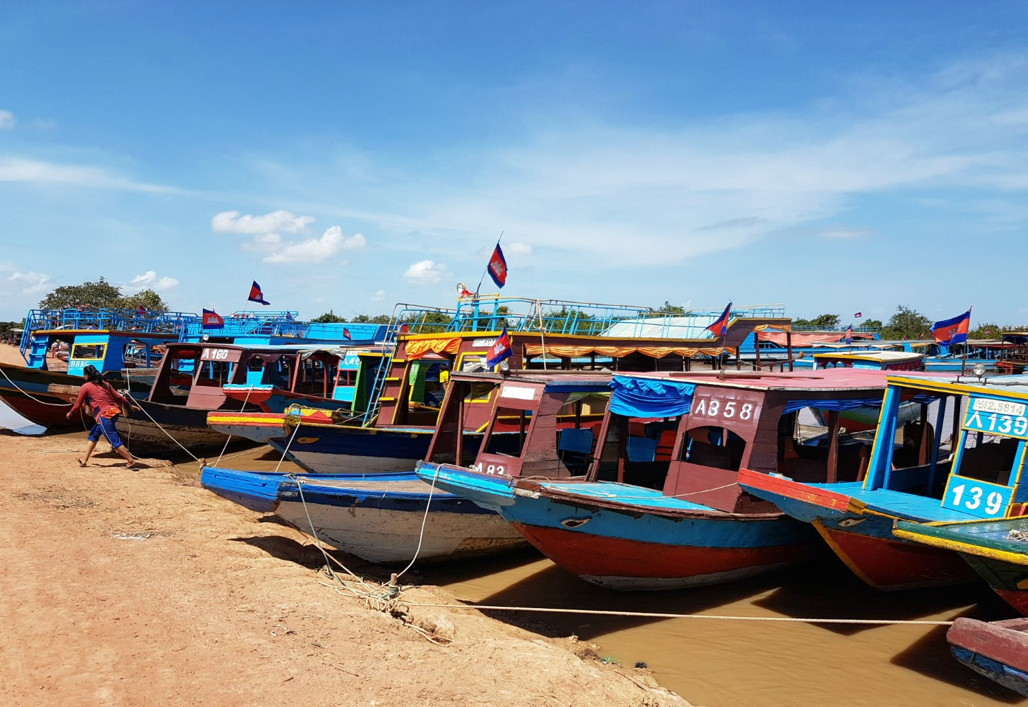 Brightly coloured boats moored on the river near Tonle Sap lake -12 reasons to visit Cambodia with kids