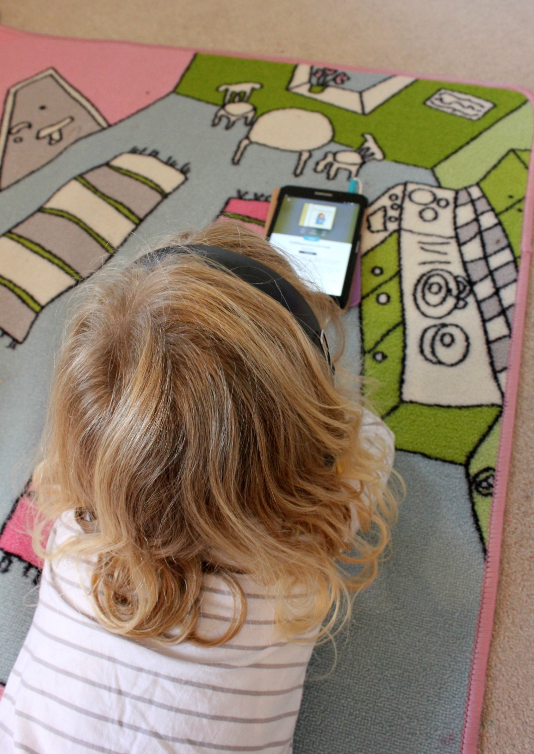 My daughter sits and listens to a story on the BookBeat app on a tablet