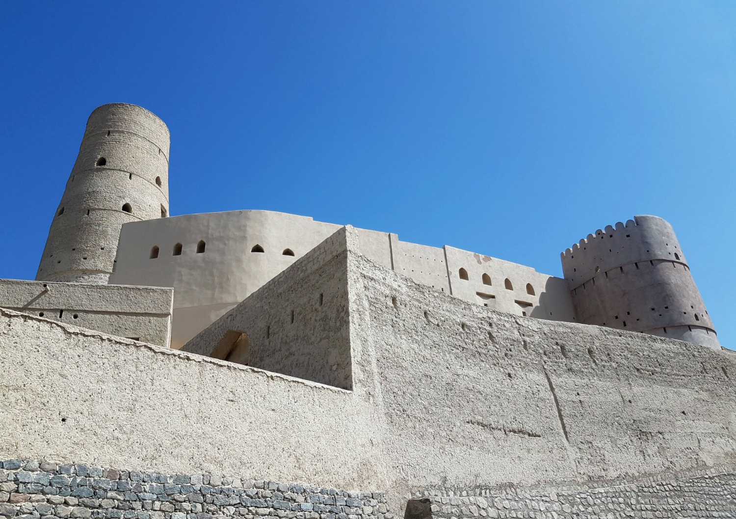 visiting Oman's forts: the white buildings of Bahla fort in Oman against a blue sky - my nine reasons to visit Oman with kids