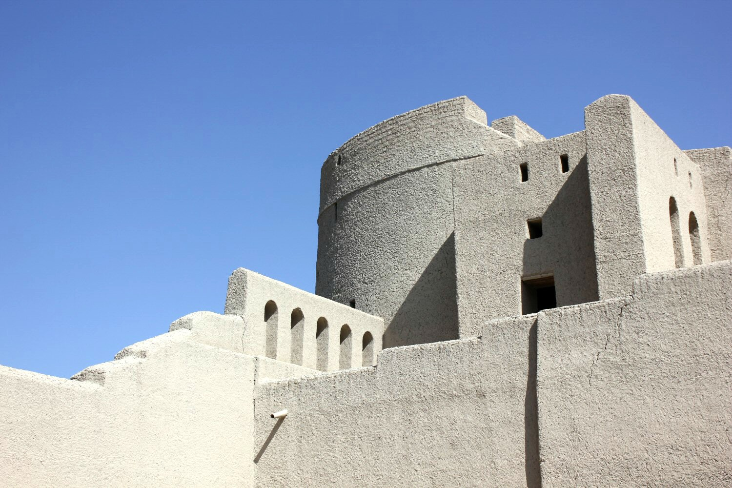 A view of the round white tower and walls of Bahla Fort in Oman against a blue sky- my nine reasons to visit Oman with kids