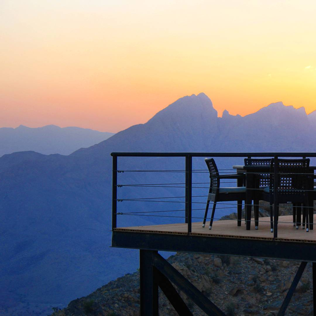 A sunset view out to the Hajar Mountains from The View Hotel in Oman, with the edge of the restaurant terrace on stilts visible with the peaks behind - my nine reasons to visit Oman with kids