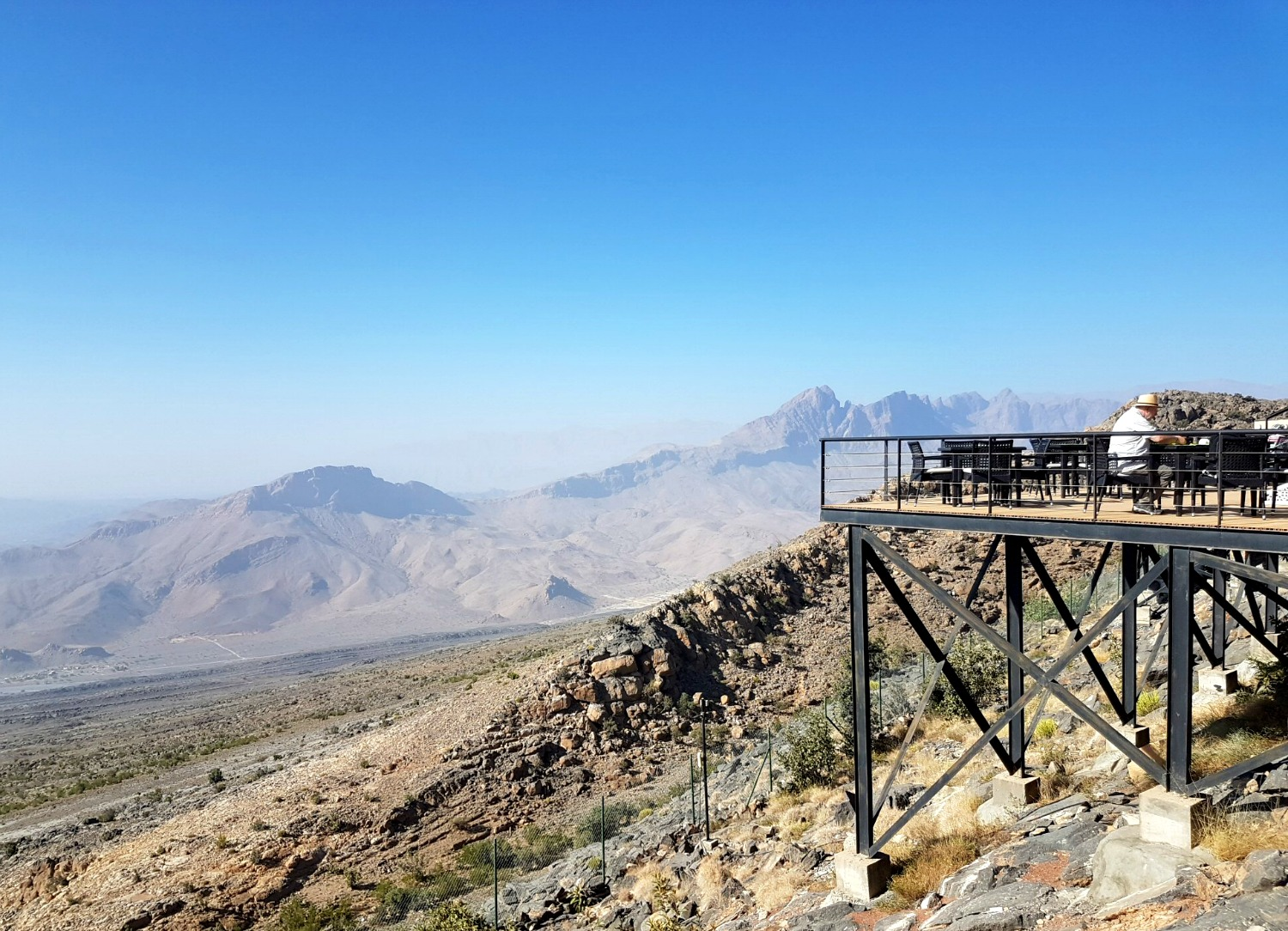 A view out to the Hajar Mountains from The View Hotel in Oman, with the edge of the restaurant terrace on stilts visible with the peaks and blue sky behind - my nine reasons to visit Oman with kids