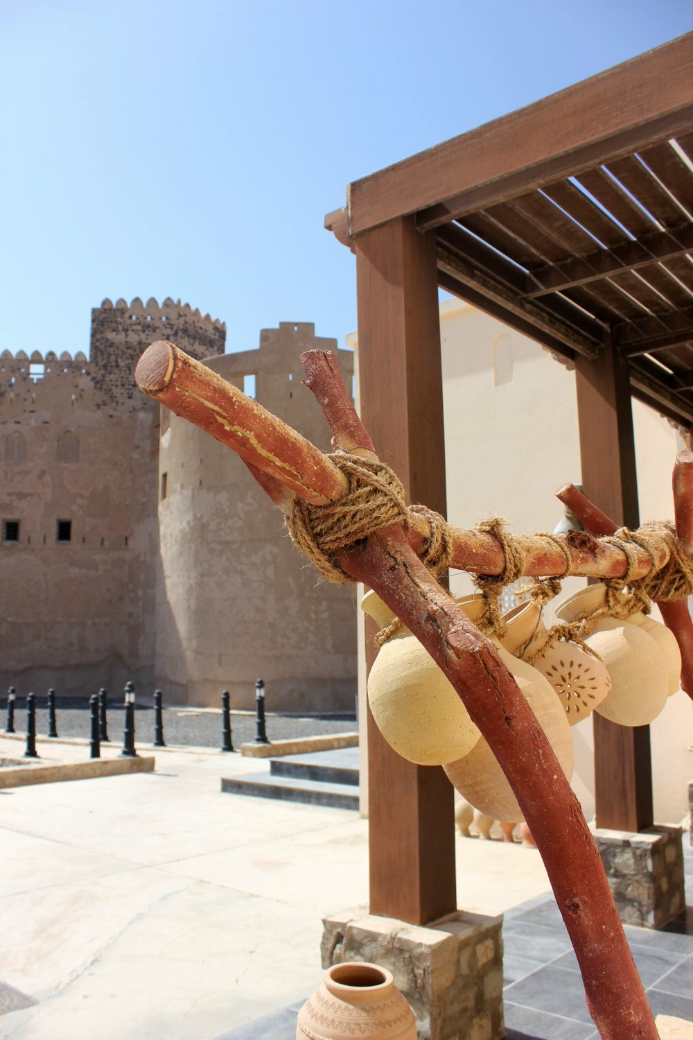 Clay water pots hang outside Jabrin Castle in Oman with the fort behind - my nine reasons to visit Oman with kids