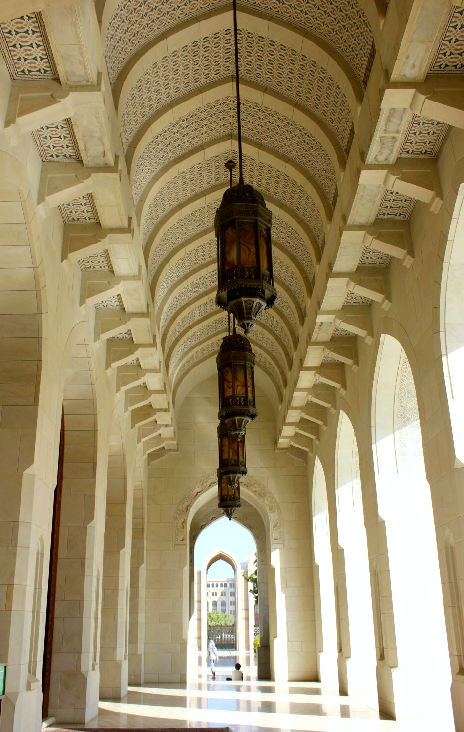 Light streams through archways along a covered walkway to another arch in the Sultan Qaboos Grand Mosque in Muscat Oman - the beautiful architecture is one of my nine reasons to visit Oman with kids