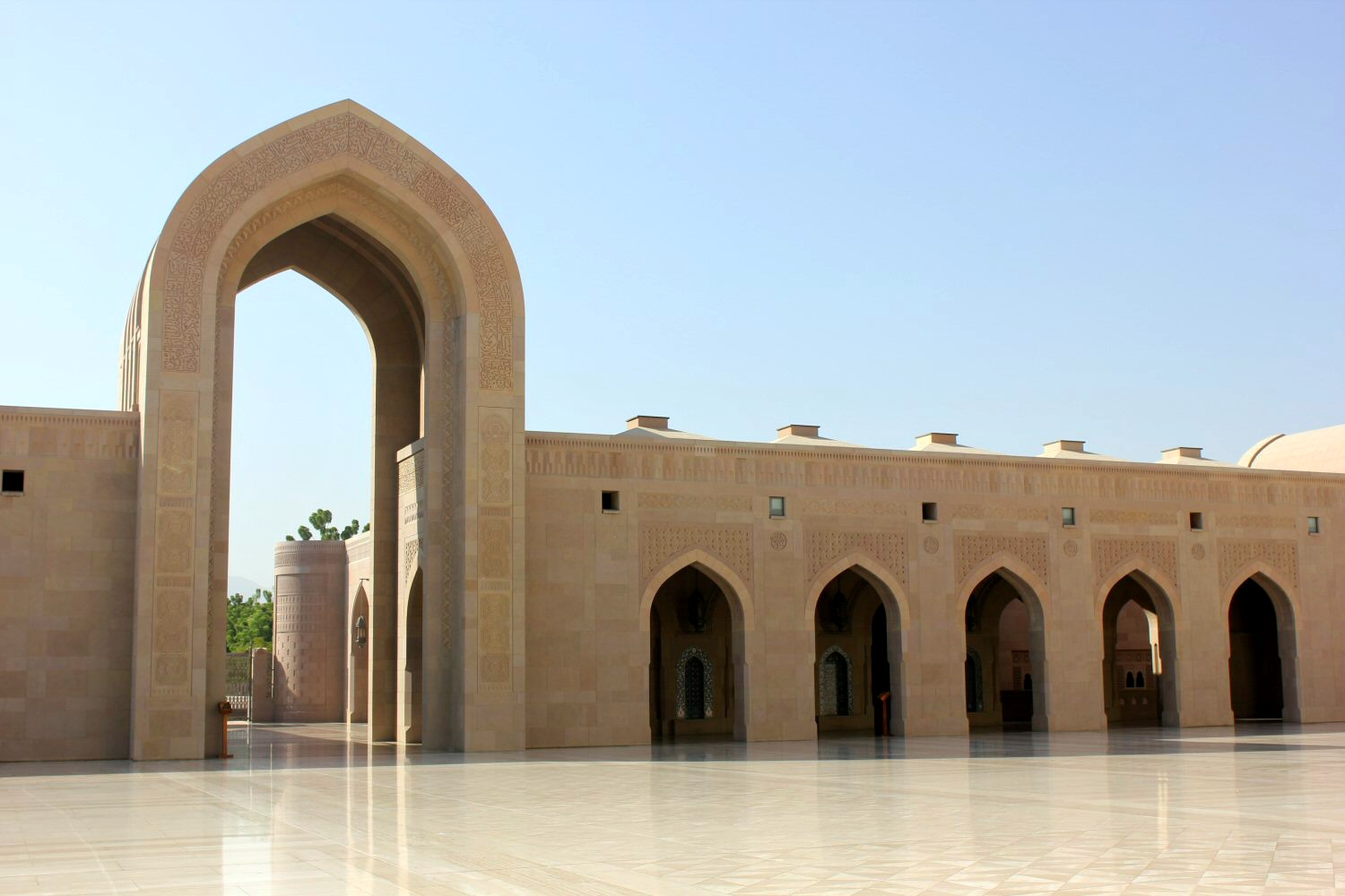 A view of an archway and sand coloured building at the Sultan Qaboos Grand Mosque in Muscat Oman - the beautiful architecture is one of my nine reasons to visit Oman with kids