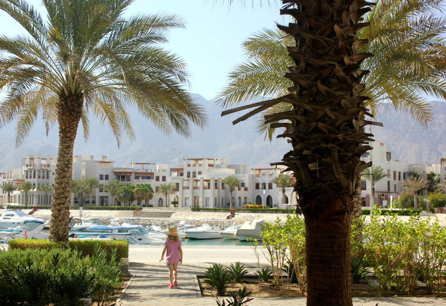 My daughter walks between palm trees at the marina of As Sifa with the white buildings and mountains in the background, not far from Muscat, Oman - my nine reasons to visit Oman with kids