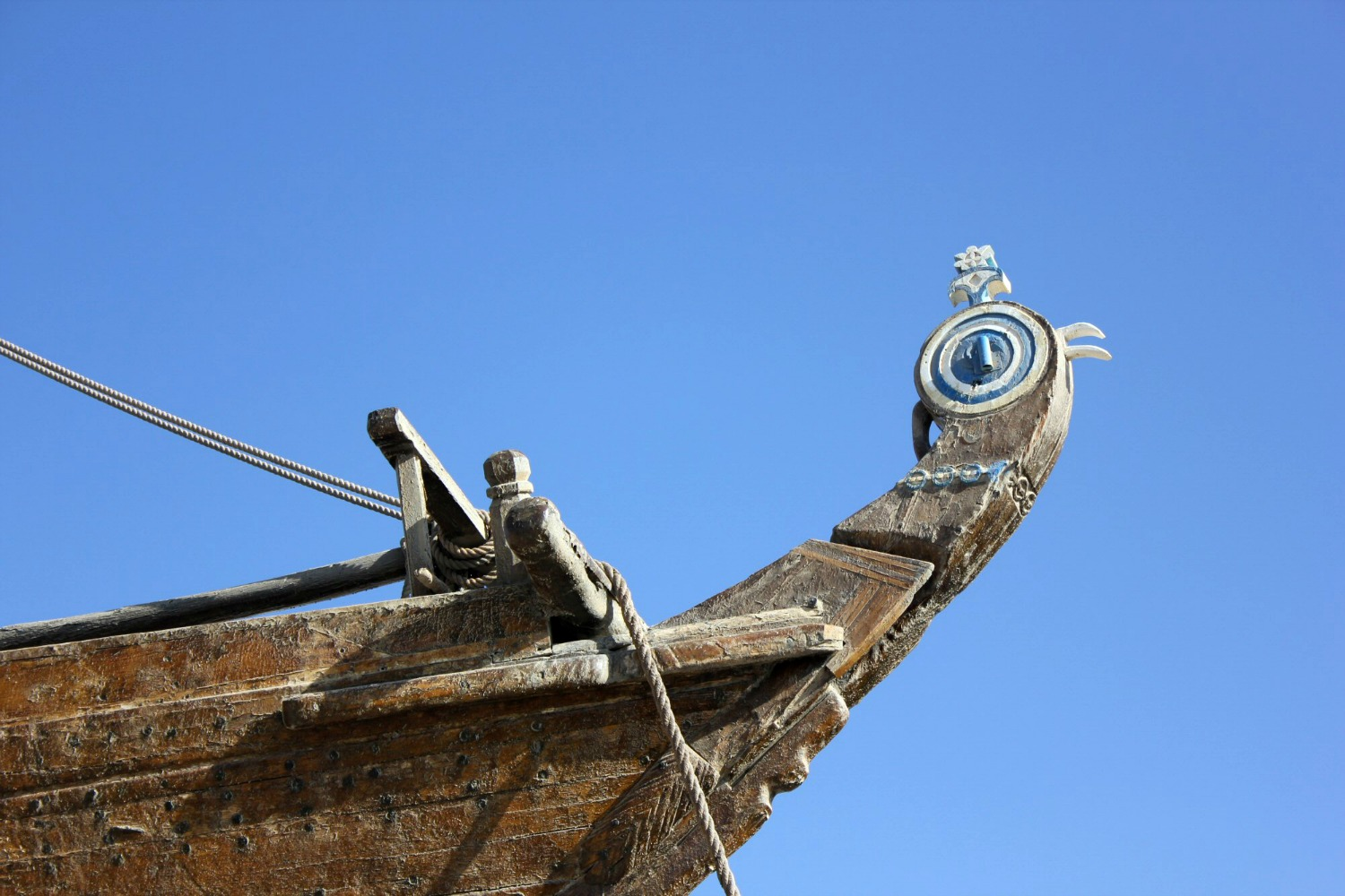 The painted prow of a historic wooden dhow boat against a blue sky at Sur in Oman - my nine reasons to visit Oman with kids