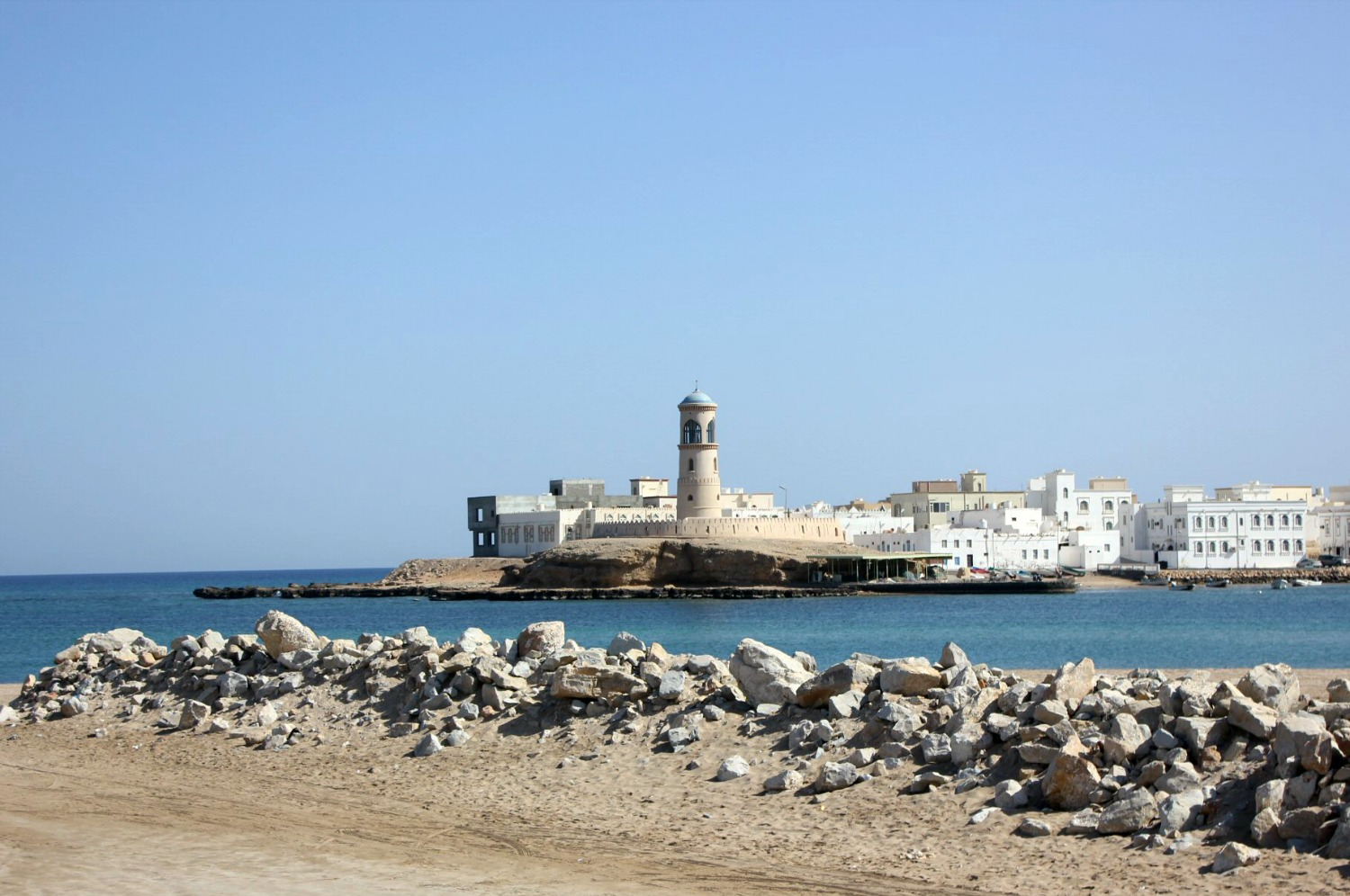 Looking across the blue water to the white and sand coloured lighthouse and buildings of Sur in Oman - my nine reasons to visit Oman with kids