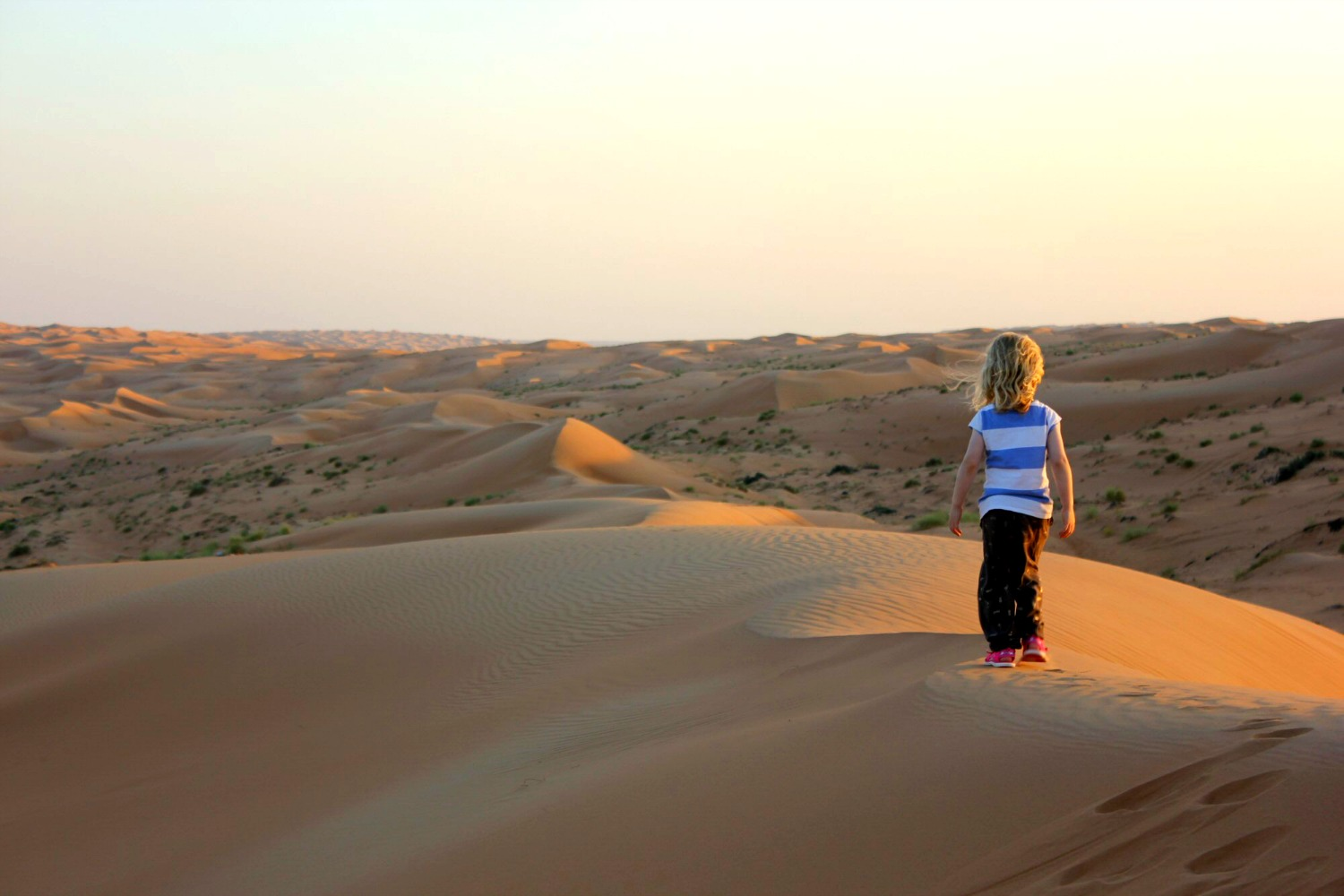 My daughter watches the sun set over the orange dunes stretching into the distance at Wahiba Sands in Oman - my nine reasons to visit Oman with kids