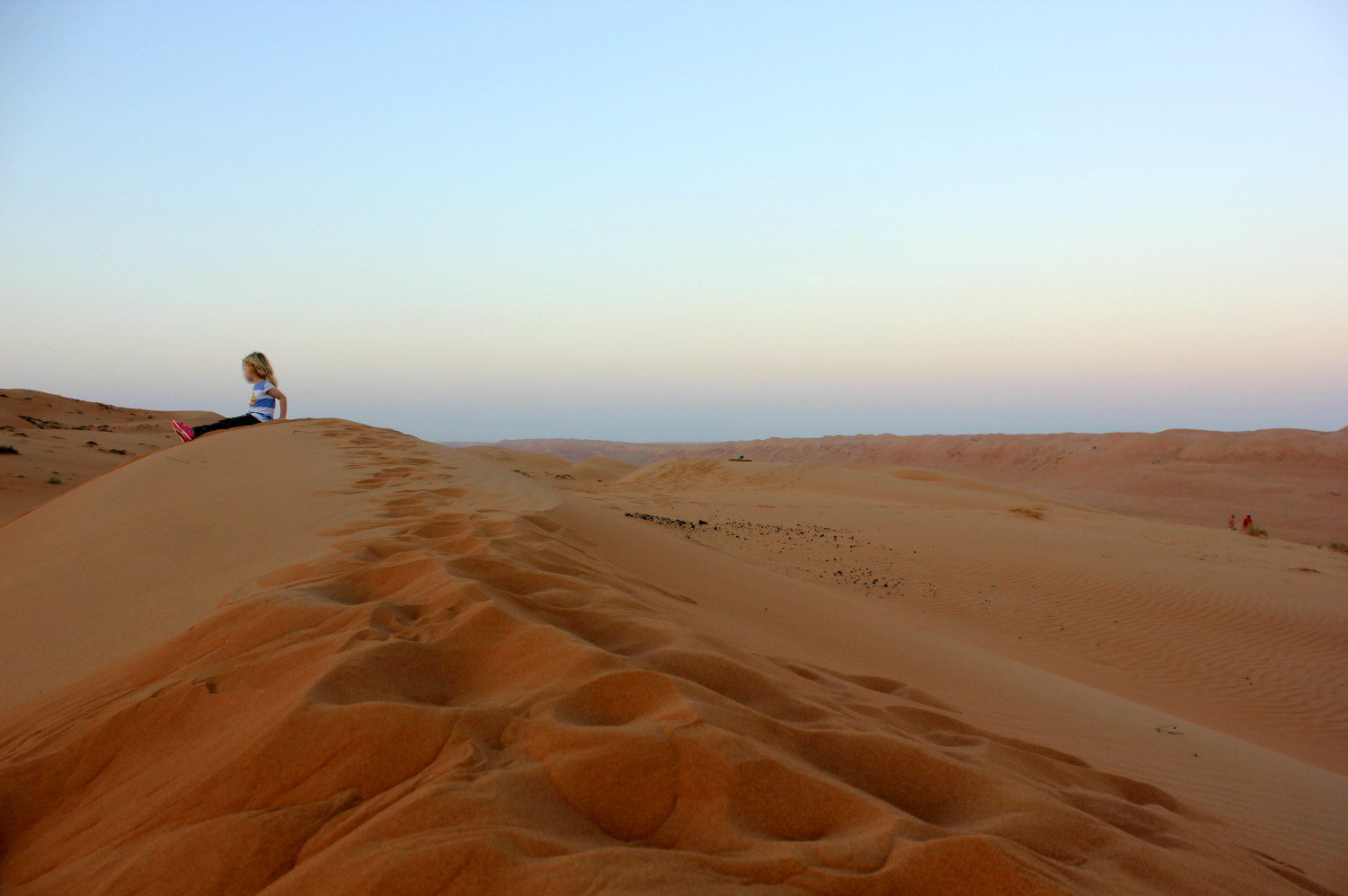 A shot of my daughter sitting on the edge of a sand dune in Oman, alone in the landscape with the start of sunset behind her - our stay in Wahiba Sands