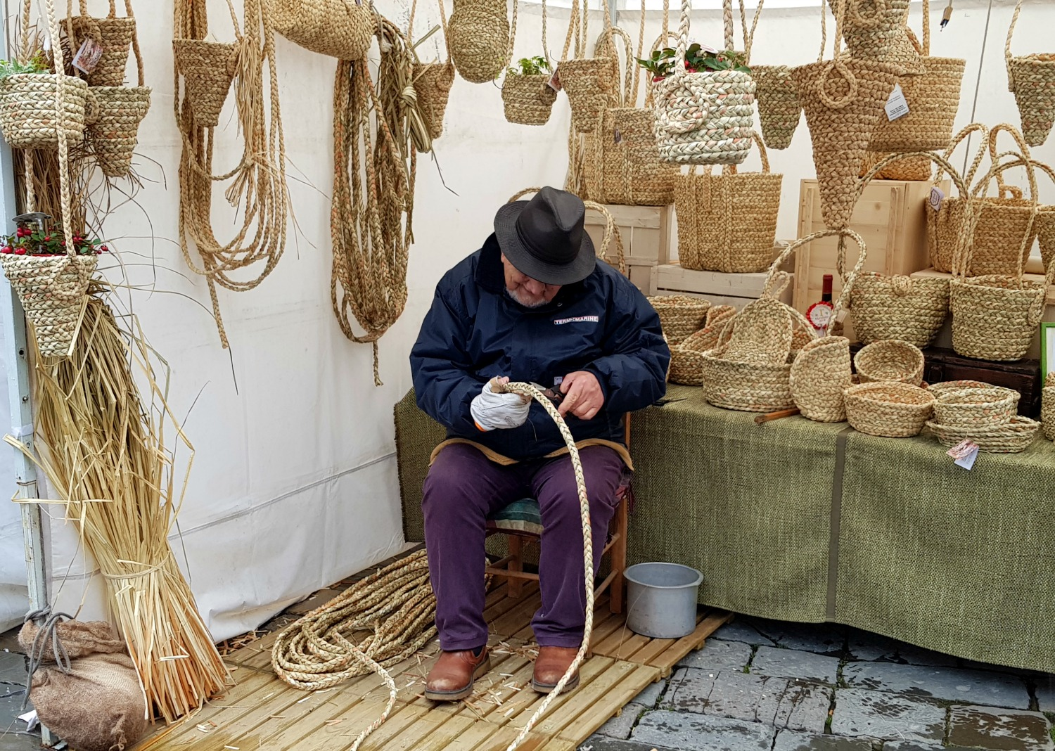 Man weaving from straw at at farmer's market in Florence, italy - my Uffizi tour with kids and gelato making day in Florence