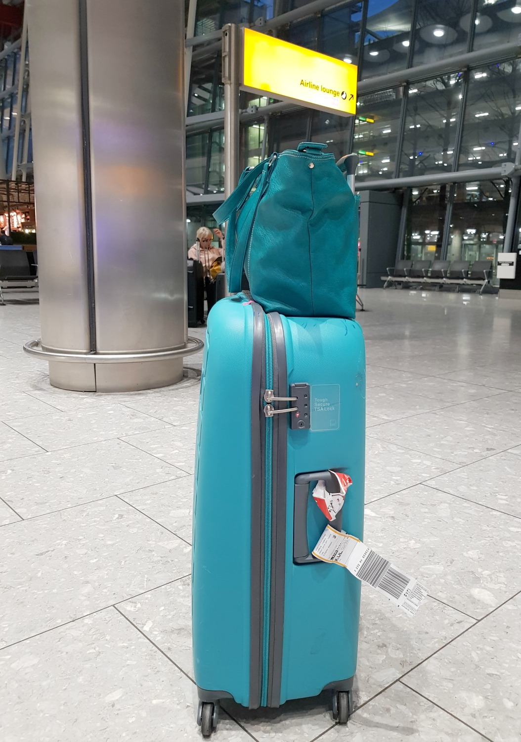 Green Mini Jen bag with special pocket slotting over the handles of a suitcase at Heathrow airport - my Mia Tui hand luggage review