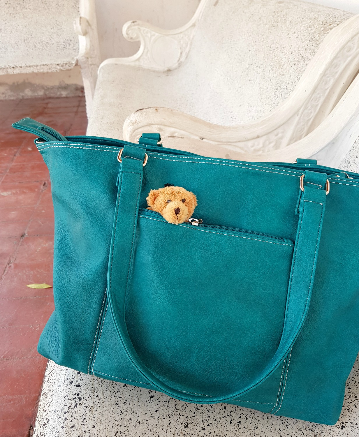 Small bear looking out of the side zip pocket on the Mini Jen bag - my Mia Tui hand luggage review