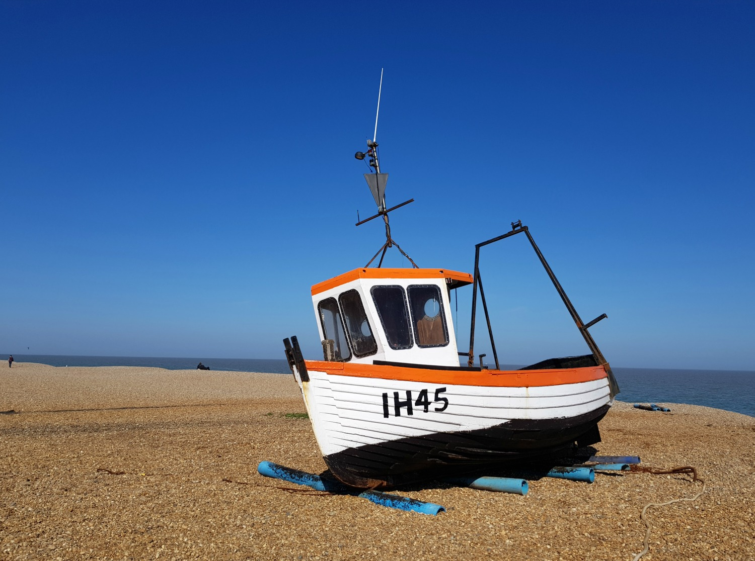 A boat beached on the shingle at Aldeburgh against a bright blue sky - one of my things to do in Aldeburgh with kids if you're visiting Suffolk