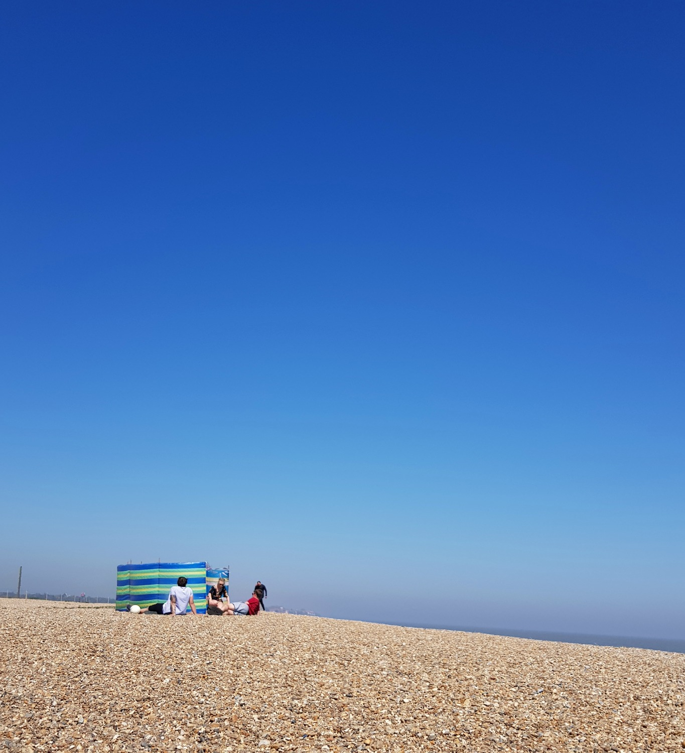 People sitting by a windbreak on the shingle beach at Aldeburgh against a bright blue sky - one of my things to do in Aldeburgh with kids if you're visiting Suffolk