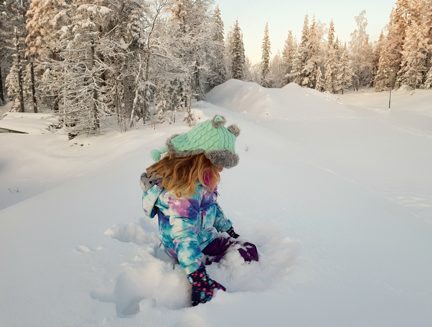 ca034245e96 My daughter in winter snow gear scoops more snow up from a drift in Lapland  -