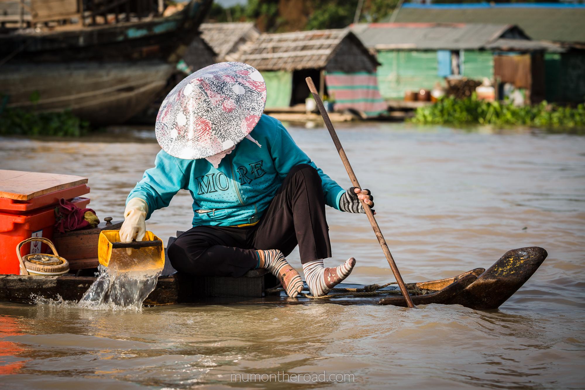 Femme vietnamienne écopant son embarcation dans un Village flottant du tonlé Sap à Kompong Chhnang au Cambodge