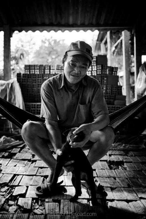 Ouvrier d'une fabrique de briques de la province de Ben Tre au Vietnam, qui se repose avec son chien