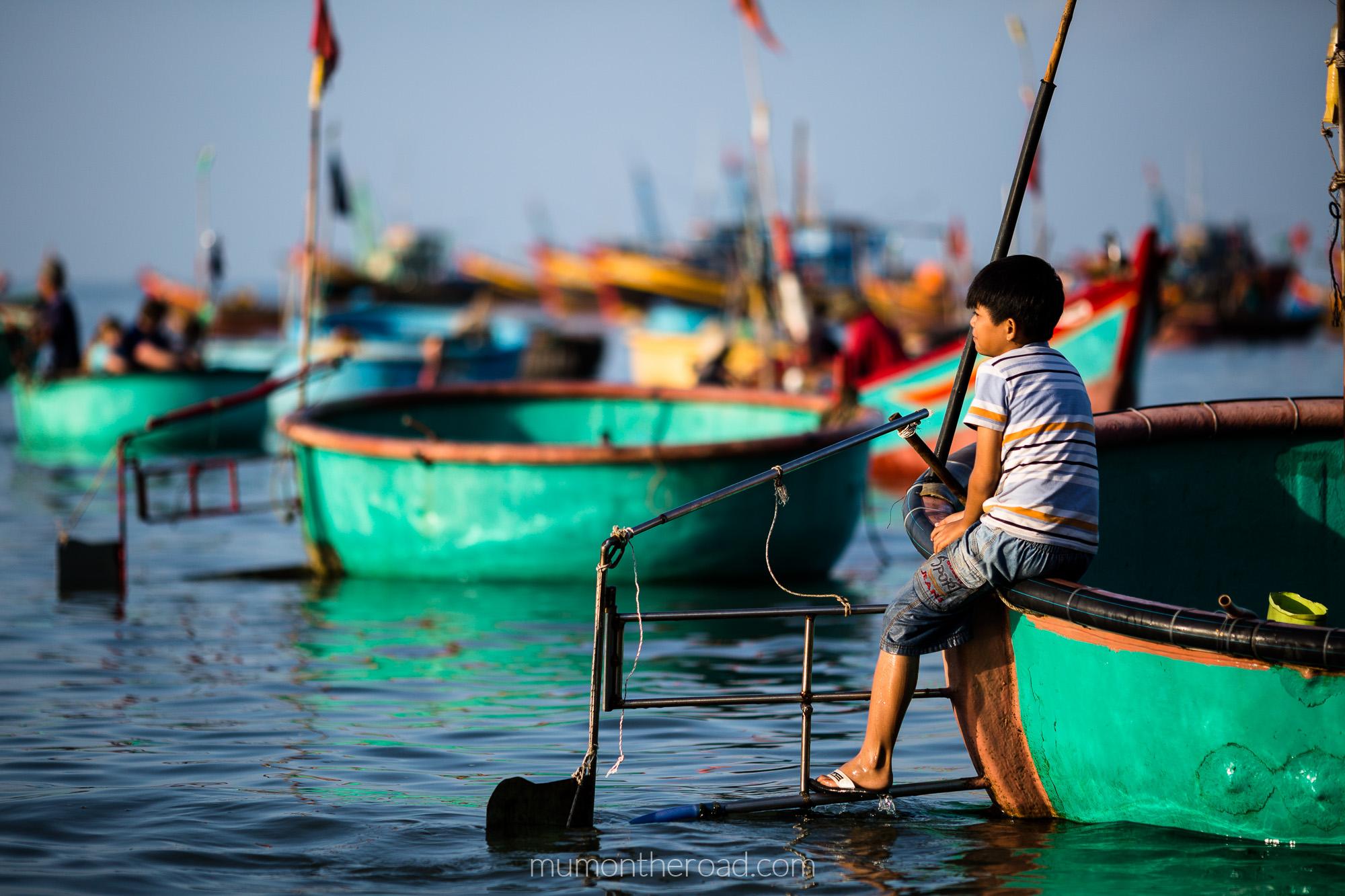 Garçon attendant son père dans un bateau panier au village des pêcheurs de Mui Ne au Vietnam