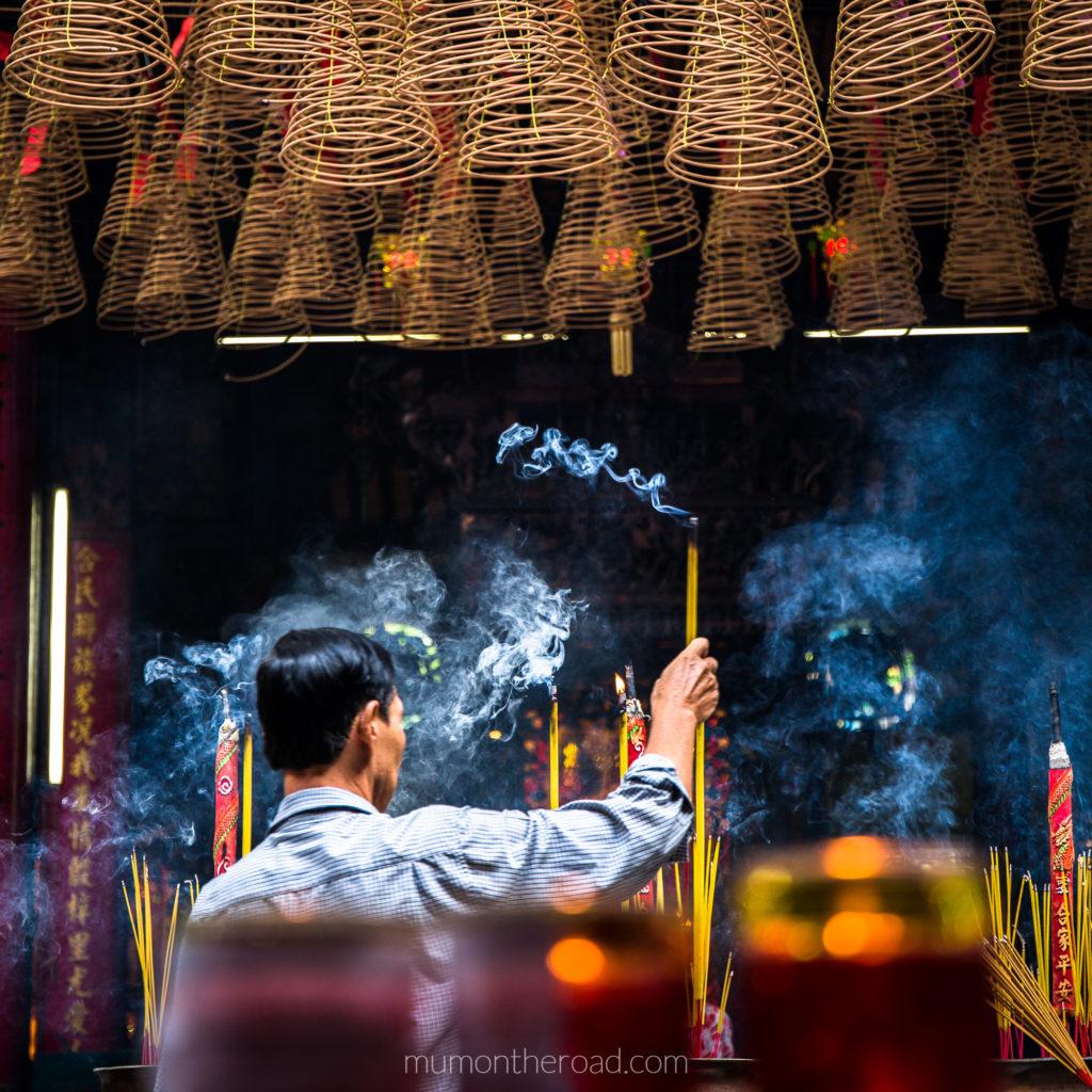 Homme brûlant de l'encens dans la pagode Thien Hau du quartier Cholon à Saigon au Vietnam
