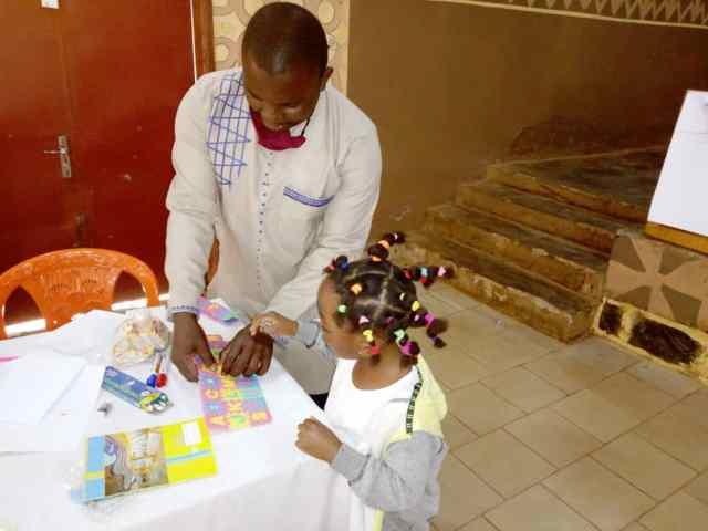 Un animateur jeunesse assistant une petite fille