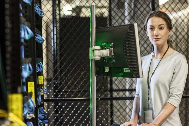 Caucasian woman technician working on computer servers in a server farm.