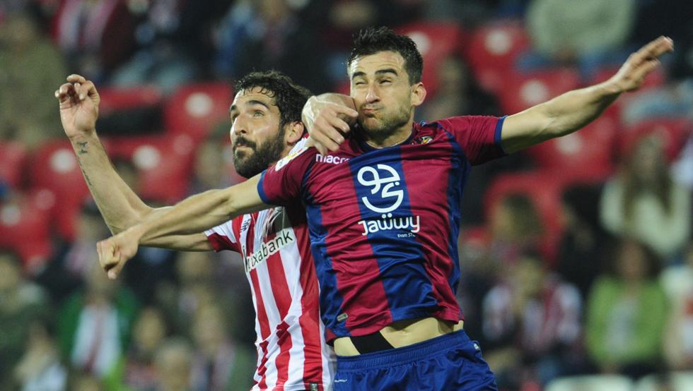 Raúl García disputa un balón por alto con Postigo, defensa del Levante.