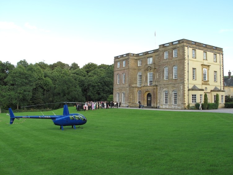 Blue helicopter G-LMBO is parked on the lawn of a large country house, group of guests in background