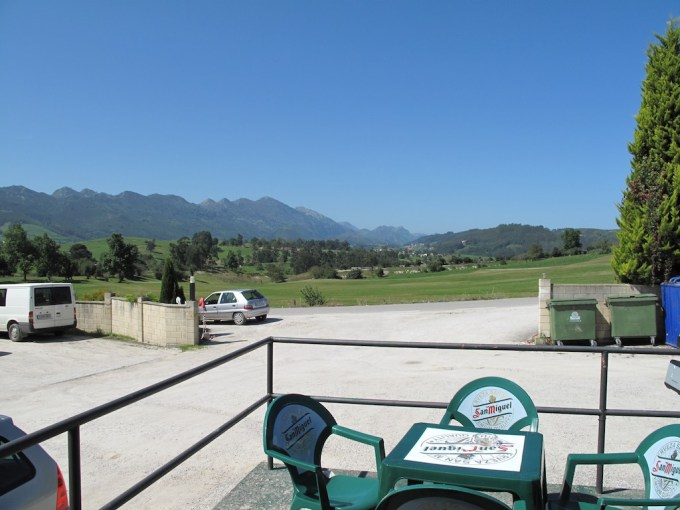 A plastic table for four stands on a deserted patio in the midday sun, blue skies and mountains in the background