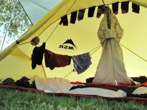Damp washing strung up inside a yellow tent