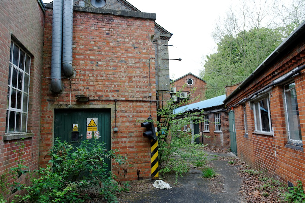 Some old traffic lights regulated traffic along this single lane between the workshops