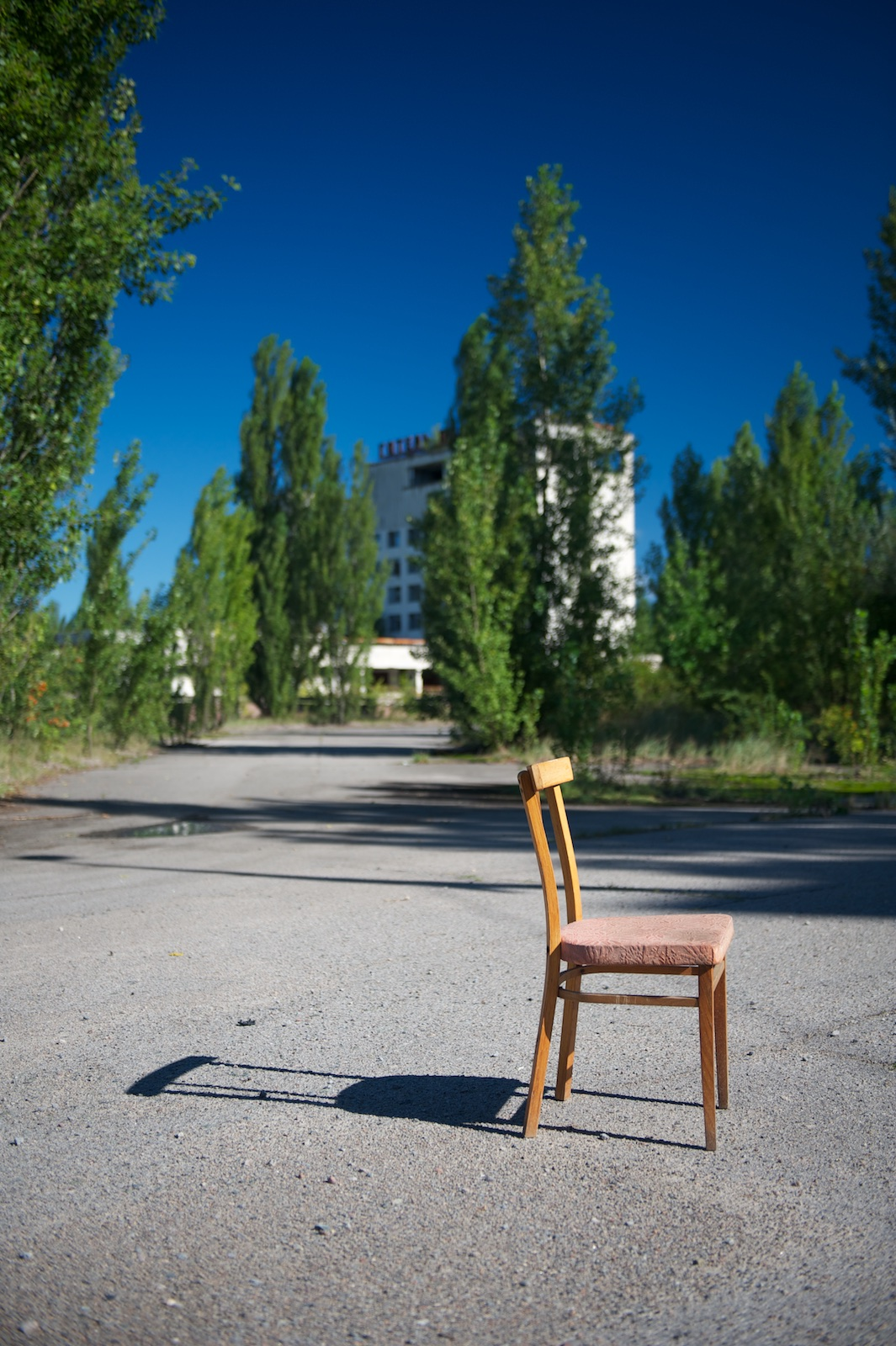 A solitary wooden chair stands in the middle of what looks like a tarmac square fringed with trees