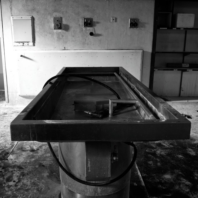 Moody black and white image of a mortuary table