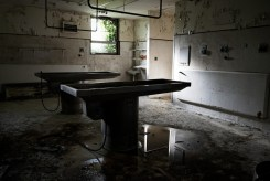 Another backlit image of mortuary tables in an obviously derelict room