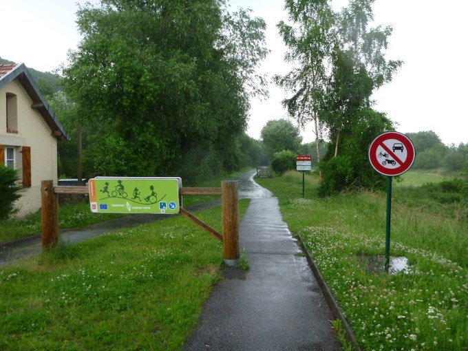 A wet cycle path disappears into the distance past a barrier prohibiting larger traffic