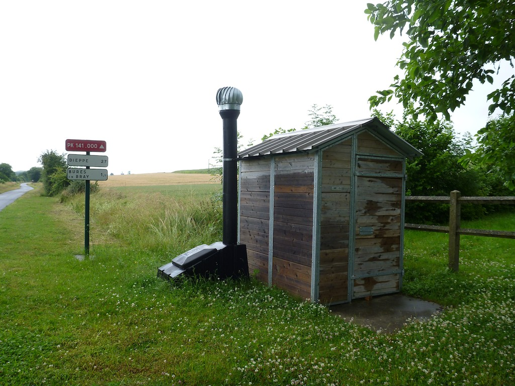 Small wooden toilet building by the side of a cycle path