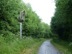 A railway signal is all that remains of a line, now surfaced for use as a cycle path