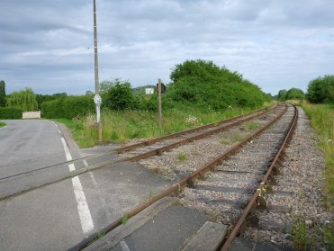 Disused train lines cross a quiet French road at an angle, soon to be removed and turned into more cycle path