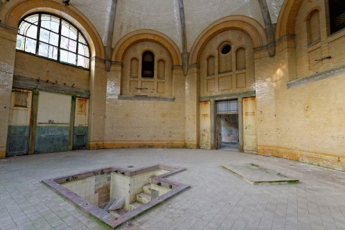 View of a vast tiled room, a small recessed tub in the floor immediately in front