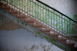 A railed flight of stairs in front of a wall whose paint is peeling, because that is what paint does.