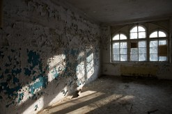 Light streams in through three windows and hits a wall whose pain is peeling