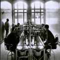 Two rows of patients sit facing each other across a bank of equipment resembling pipes and masks