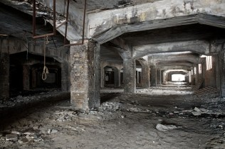 Photo of cavernous arches beneath the boiler house. A noose has been fitted to some metalwork.