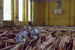 Several lamps have fallen to the crumbling wooden floor of a large hall, while a mural of a gymnast adorns the far wall behind a basketball hoop