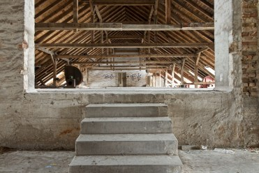 Stairs leading into the very top floor under the rafters of a building