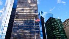 Stars and Stripes flutter in front of a shiny office building