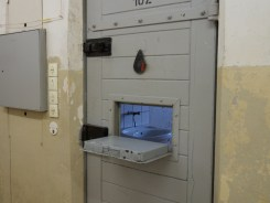 Looking through a hatchway in a locked cell door reveals a small sink against one wall