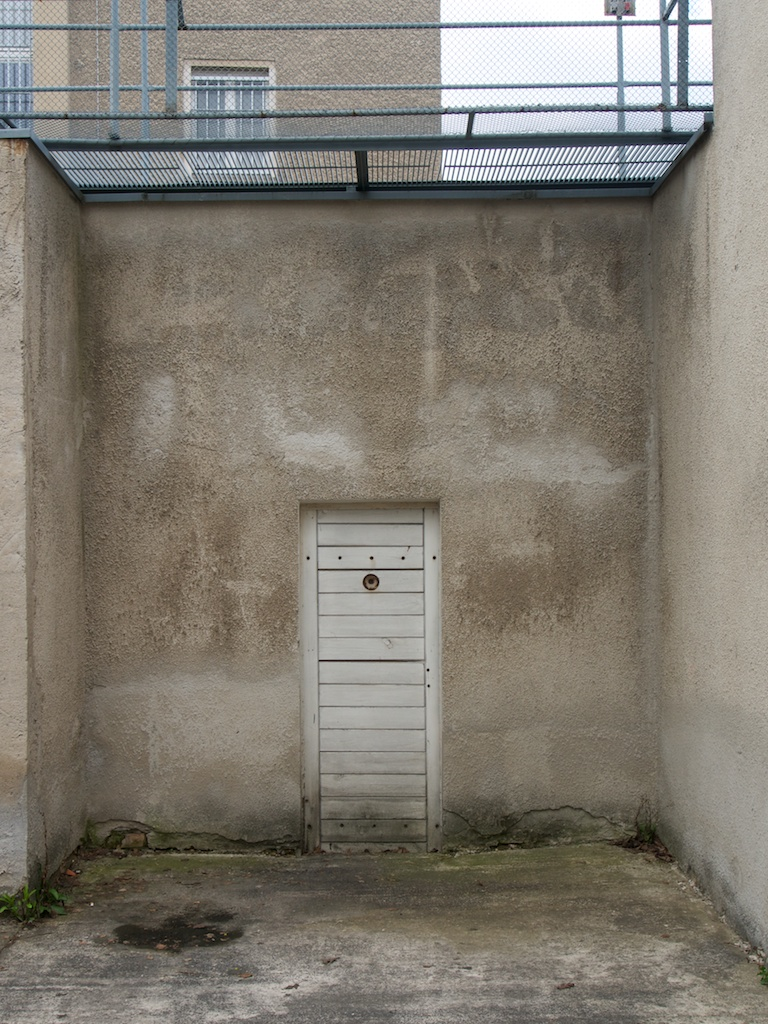 A doorway leads to a narrow yard with high walls topped with barbed wire walkways